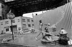 A grandmother cools off in a wading pool beside an open fire hydrant beneath the Manhattan Bridge, Brooklyn, New York, Summer (Photo by Eugene Richards) Walker Evans, Tim Walker, Herbert List, Mary Ellen Mark, Spencer Tunick, Lee Friedlander, Karl Blossfeldt, Stephen Shore, August Sander