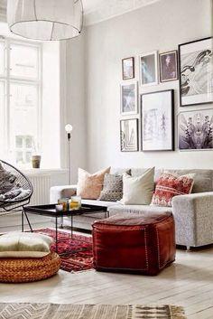 Les murs et sols clairs sont joliment rehaussés de touches de couleurs avec de nombreux coussins, un pouf et un tapis pour un ensemble très réussi.