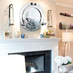 Love the look of the Nickel Porthole Mirror above the fireplace mantle. It makes a beautiful focal point for the nautically inspired decor. Nautical Wall Decor, Nautical Home, Porthole Mirror, Fireplace Mantle, Fireplaces, Money, Inspired, Beach, House