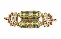 A GEM-SET ENAMELLED ARMBAND (BAZUBAND)  NORTH INDIA OR DECCAN, 19TH CENTURY  Formed by two rectangular containers of hexagonal section, joining along their long side, with articulated openwork floral panels at either sides, the front set with diamonds and foiled red gems, the reverse with floral enamelled decoration on white ground, each of the containers opening to reveal a small compartment 2 7/8in. (7.4cm.) long