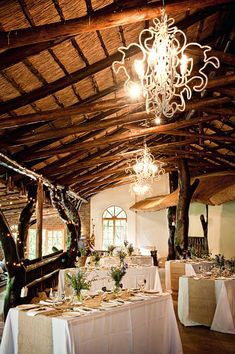 rustic South African lodge with chandeliers> love the rectangular tables.