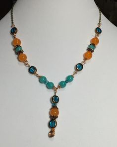 Pendant styled necklace crafted from rare South American Orange Topaz and Brazilian Aquamarines set on copper wire. Pendant is coiled copper with topaz and glass. Necklace is approximately 18 inches l