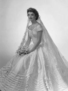 12 Septembre 1953, Newport (Rhode Island), Jacqueline BOUVIER épousait J.F.KENNEDY. Elle portait le voile de sa grand-mère et une robe ayant nécessité 46 mètres de taffetas de soie ivoire. Son choix d'ANN LOWE, une créatrice afro-américaine était courageux. Jacky aurait souhaité une robe près du corps mais, pour la première fois, elle se plia à la volonté de la famille Kennedy. Ce jour-là elle devint une véritable icône de la mode. * Jaimemarobe.com * Votre robe de mariée est précieuse.