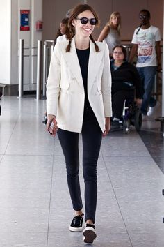 May 19th 2014. At Heathrow Airport wearing a white blazer jacket, black top, black skinny jeans and black Superga sneakers with black sunglasses.