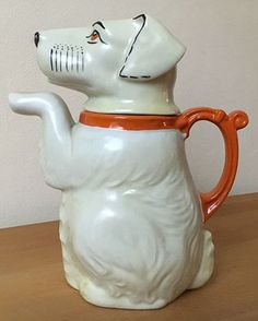 vintage teapot in shape of begging dog sitting up with raised paw forming spout, head as lid, c. 1930s-1940s, ceramic