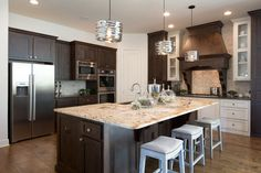 Rich dark wood gives the kitchen body as a muted backsplash and creamy island add texture without overtaking the space. The stainless steel appliances are complemented by the reflective lighting making everything feel at ease and updated in this transitional home.