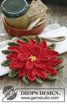 "DROPS Christmas: Crochet DROPS pot holder in ""Paris"" with decorative flower in ""Cotton Viscose""."
