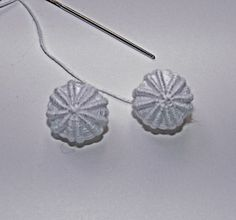 Yorkshire Buttons are basically an extension of an embroidery stitch called a ribbed wheel. (Also known as ribbed spider's web, back stitched spider's web, woven wheel or woven spot). Somewhere in ...