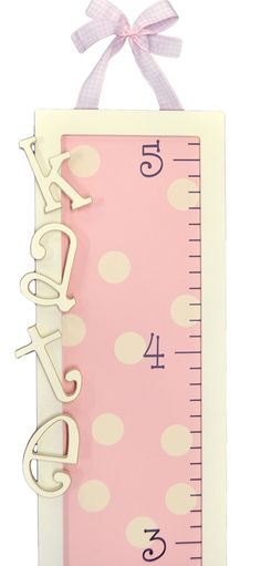 "Pink Polka Dot Wooden Growth Chart by New Arrivals IncTrack your child's growth to five feet tall with this hand painted, wooden growth chart from New Arrivals, Inc. Make it truly personalized with 5"" letters! Includes coordinating ribbon.Tori Swaim, owner and designer at New Arrivals, Inc., began the company with an idea for a box that would cleverly disguise those pesky, but necessary, plastic baby wipe containers. She created a gorgeous solution that fit in well with her thoughtfully…"