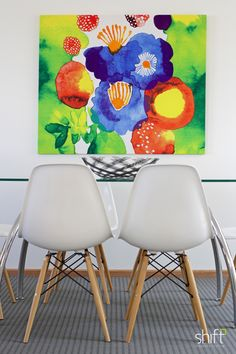 Bright  artwork,  white Eames  chairs with glass dining table. Property Styling #styledbyshift