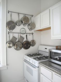 Small apartment godsend! Wall storage for pots and pans from IKEA..... And it's SUPER cheap.