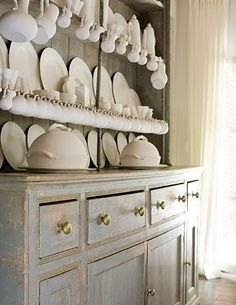 white hutch with all white dishes