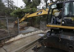 Los Angeles County Flood Control District crew member David Martinez uses an excavator to keep a flood inlet clean in Glendora, Calif., on Tuesday, Jan. 5, 2016. Persistent wet conditions could put some Los Angeles County communities at risk of flash flooding along with mud and debris flows, especially in wildfire burn areas. (AP Photo/Damian Dovarganes)