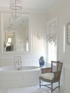Breathtaking luxurious bathroom with oval freestanding tub, traditional decor, white marble, and paneled walls in French chateau (The Enchanted Home).