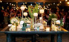 Arreglo floral de la mesa hall, base de espejos con candelabros, velas y flores en verde lima, blanco y peach. Finca El Campillo