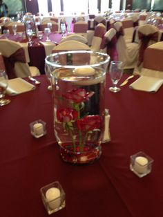 Hurricane vase with submerged Fire & Ice roses and floating candle.