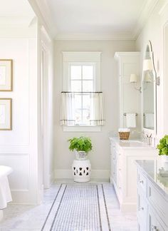 A white and gray bathroom features separate washstands topped with polished marble fitted with square curved sinks and vintage hook and spout faucets placed under white arched mirrors illuminated by Vendome Single Sconces.