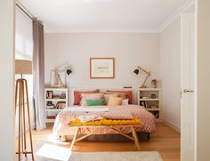 Dormitorio principal con cama, cabecero, banco y ropa de cama en rosa y amarillo_10426
