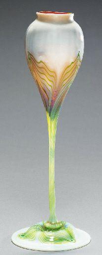 """Copa con forma de flor   Tiffany Studios, circa 1907, 11 1/8in. (28.3cm.) high, engraved L.C.T. 4546B. """"Favrile Glass"""", un tipo de cristal ideado por Louis Comfort Tiffany, patentado en 1894. Es diferente de los demas cristales iridiscentes porque el color y el brillo esta no solo en la superficie sino tambien en su interior. Se subasto en Christie´s  en diciembre de 2001 adjudicandose  por 8.225 dolares.  Mide 28,3 cms Diseñada por Louis Comfort Tiffany para Tiffany Studios"""