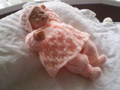 Hand knitted 10 inch Ashton Drake/similar doll clothes  This 4 piece outfit has been hand knitted in new peach 4 ply yarn/    The patterned matinee coat has 2 buttons to front opening.    The trousers