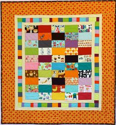 """Pink Chalk Studio's """"I Spy Lollipop Quilt"""" - 39"""" x 42"""" inches, just right for a baby gift or young toddler's playmat.  I love the construction of this - the bright """"I Spy"""" rectangular blocks against solid fabrics, a small strip of light sashing followed by a pieced border of the solids, followed by another thin line of light sashing again.  Then this vibrant but not overwhelming print and a dark binding to set it off.  It's a mastery of design!"""