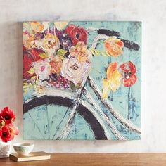Who knew a bicycle could grow flowers? Our colorful canvas painting, both playful and pretty, will make you smile each time you walk by it. Hang it in a prominent place on your bedroom, family room or entryway wall. #canvaspaintingart