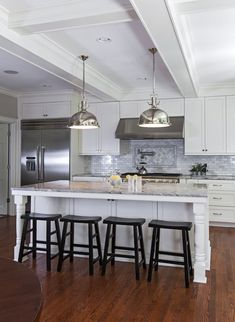 Open concept kitchen with white shaker cabinetry accented with nickel pulls along with gray marble counters and a mini brick marble tiled backsplash.