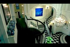Grayson Manor's main entry. The back stair case is visible in this view. Though it rarely seems to be used in filming. The vases and pedestals used by the front staircase change frequently. The details of the cage on the chandelier surround are visible. The only criticism of this set is the upstairs hall width. For a mansion this hall seems very narrow.