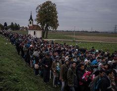 Мигранты в сопровождении словенской полиции проходят мимо церкви, направляясь в регистрационный лагерь на окраине словенского городка Добова.  (The New York Times / Сергей Пономарев - 22 октября 2015)