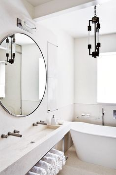 white bathroom, oversized circle mirror, lighing fixture, open shelves, stone sink.