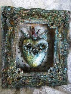 RESOLVE is a painted and textured handformed and painted heart in a framed tin box. Two metal swords are crossed and piercing the heart. Three
