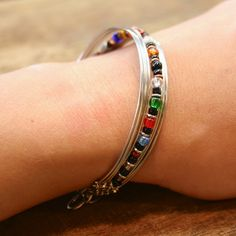 Fair Trade Wire Beaded Bracelet — handmade in Kenya — find it at Fair & Square Imports — This classic silver-plated copper wire bracelet features a row of multi-colored beads and spectacularly woven, flattened ends.