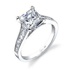 SY711    This dazzling 18K white gold diamond engagement ring features a 1 carat princess cut center diamond. Accentuated by surrounding round diamonds and baguette diamonds down the shank, ALSO very close! Beautiful ring