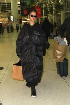 She traipses through JFK wearing an oversized, black Jessica Walsh puffer coat, oversized hoops, and Adam Selman x Le Specs sunglasses. - MarieClaire.com