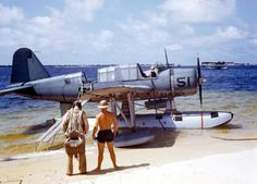 OS2U Kingfisher floatplane at the edge of the seaplane ramp at NAS Pensacola, Florida, early 1941. In the distance, a Consolidated P2Y flying boat is visible laying off shore.