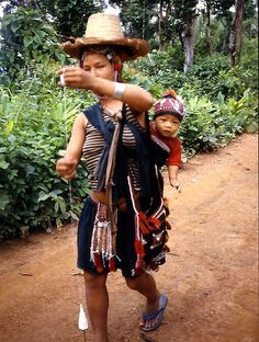 Babywearing photo || U-Lo Akha woman handspinning with her child on her back