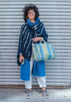 """Audra""""I am wearing my favorite indigo hand-blocked Malian wrap which I purchased from the artist 15 years ago, a small indigo scarf from Senegal, a vintage Liz Claiborne (LizWear) pinstriped jumpsuit, an all purpose Zara denim duster found at Salvation Army, and my trusty Pumas.I just need to be comfortable in my clothes at all times. I also look to the way indigenous people around the world cover themselves; layers of prints, textures, and patterns that serve a purpose but are also…"""