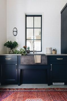 Modern kitchen design with black kitchen cabinets + #blackwindowtrim + #vintagerug #blackkitchen