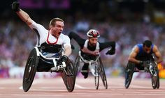 Mickey Bushell of Great Britain crosses the line to win gold in the Men's 100m - T53 Final.