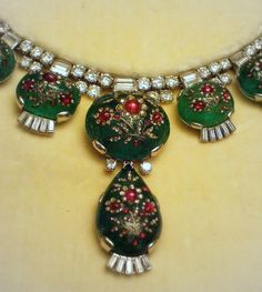 CARTIER London, 1937.Necklace and earrings.  The cabochon emeralds inlaid with ruby and diamond flowers are Indian work of the 19th century, set in Western style with baton diamonds.