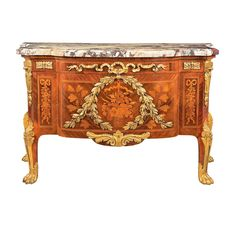 Transitional Louis XV/XVI Style Gilt-Bronze Mounted Kingwood and Satinwood Commode Attributed to Maison Krieger, late 19th century The fleur de peche rectangular marble top of break front outline with canted front corners, above a conforming case enclosing a false frieze drawer decorated with a ribbon knot, over two marquetry inlaid drawers with a central flower filled basket surrounded by a laurel wreath and flanked by oak branches and pendant floral garlands, raised on short cabriole legs…