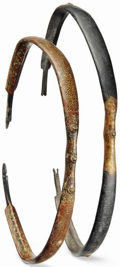 Indian (North) kaman (bow), 18th to 19th century, typical Turkic form, the first with polychrome painted decoration composed of a lattice of palmettes and floral scrolls to its limb (sal), shoulder (kasan) and grip sections, the second painted black with its grip and kasan gilded and applied with rosettes, the larger 22¾in. (57.8cm.).