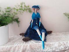 Joli camaïeu de bleu, canard et turquoise, pour cette élégante poupée de tissu. Vêtue dun pantalon agrémenté dun galon à sequins,dune jupe asymétrique en voile festonné, dun corsage en mousseline, de gants et bottes en velours. Bijoux en strass turquoise, et une breloque à la