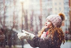 Little girl stretches her hand to catch falling snowflakes. royalty-free stock photo