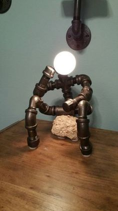 Custom built the Thinker desk lamp. LED version also available. This lamp can rest on a variety of objects (books, rocks, etc) or it. It can