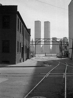 Light and shadow with railroad tracks and 19th century brick warehouse against the World Trade Center looming across the Hudson.March 1975