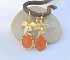 I love the orchid charm:)  Pumpkin Orange Drop Earrings with Gold Orchids  Fall by RusticGem. , via Etsy.