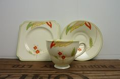 Doulton deco: unnamed tea trio, V1530, c1935 (8). Stylised floral and tree design in yellow, red and green, also to inner cup rim, with amber highlights and green trim.