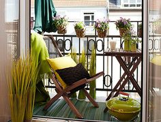 A wonderful combination of hanging plants with your small table and chair on the balcony. Add a color scheme to make everything look pleasing to the eye. The stripes on the carpet also add to the illusion of widening the floor space.