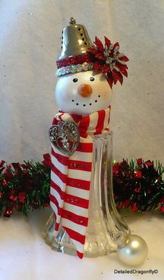 Vintage Salt Shaker Snowman Christmas is in the air! This snowman is dressed up fancy, wearing a red and white striped scarf with a touch of glitter and a sparkly heart. The top hat is vintage silver with red glitter, silver sequins, and a red & silver poinsettia. Hand painted face complete with a carrot like nose and cheery rosy cheeks. Shaker filled with faux snow. Clear coat finish over glitter and face to protect the design. Approximate size is 3 wide x 8 tall. Will ship in 1-3 busi...